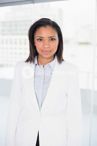 Stylish young dark haired businesswoman posing looking at camera