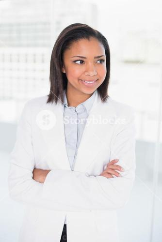 Pensive young dark haired businesswoman posing with arms crossed