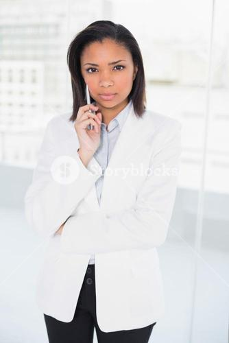Lovely young dark haired businesswoman posing looking at camera