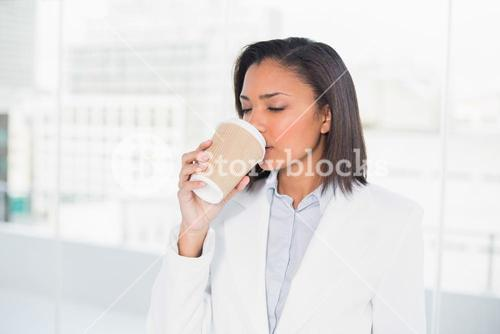 Cute young dark haired businesswoman enjoying coffee