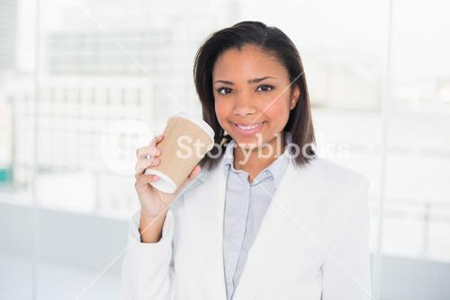 Delighted young dark haired businesswoman holding a cup of coffee