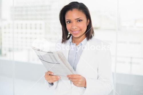 Amused young dark haired businesswoman holding a document