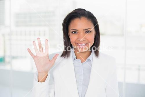 Pretty young dark haired businesswoman waving her hand