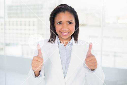 Pleased young dark haired businesswoman giving thumbs up