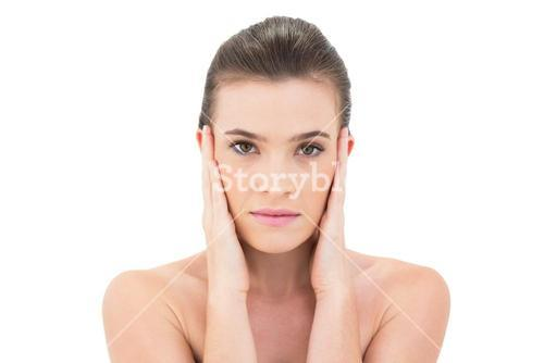 Serious woman touching her face