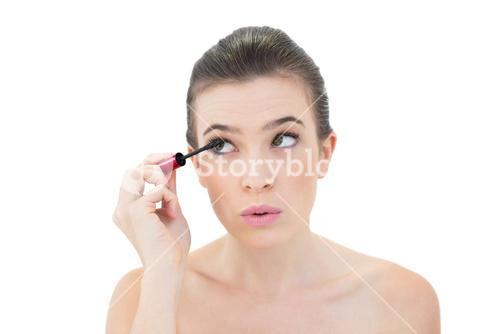 Concentrated natural brown haired model applying mascara
