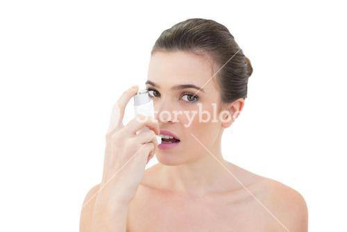 Beautiful natural brown haired model using an asthma inhaler