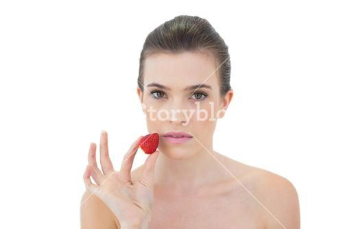 Serious natural brown haired model holding a strawberry