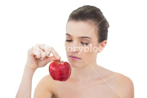 Charming natural brown haired model holding an apple