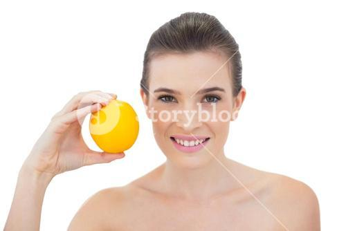 Laughing natural brown haired model holding an orange