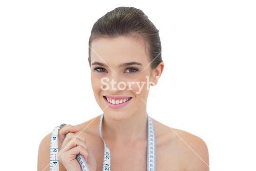 Playful natural brown haired model wearing a measuring tape around her neck