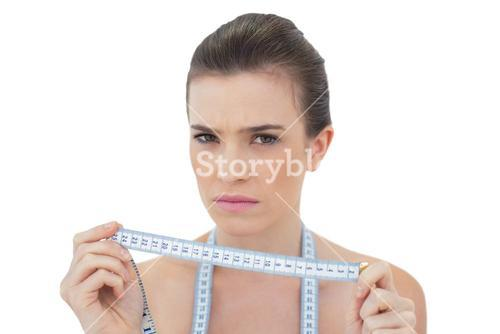Frowning natural brown haired model holding a measuring tape