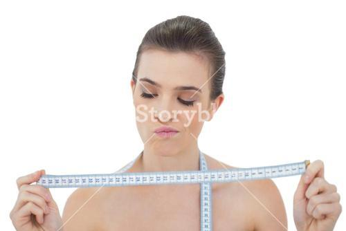 Wondering natural brown haired model looking at a measuring tape