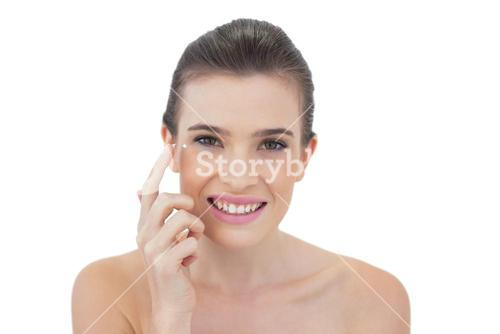 Attentive natural brown haired model applying face cream