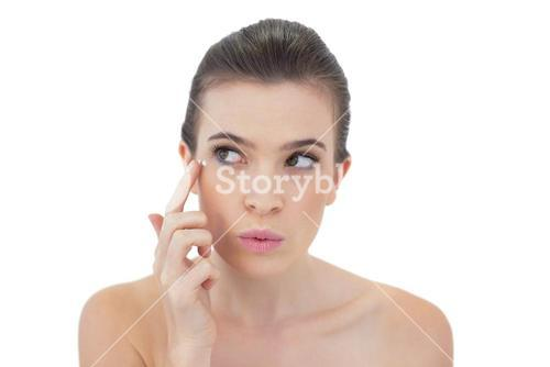 Pouting natural brown haired model applying face cream