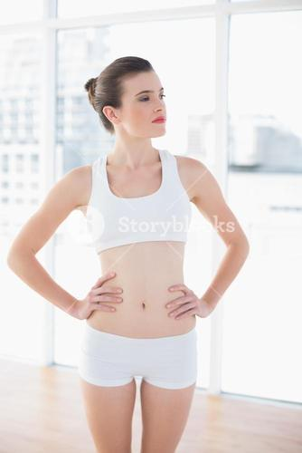 Unsmiling fit brown haired model in sportswear posing with hands on the hips