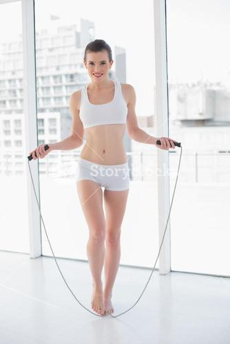 Playful fit brown haired model in sportswear using a skipping rope