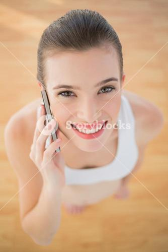 Gorgeous fit brown haired model in sportswear making a phone call