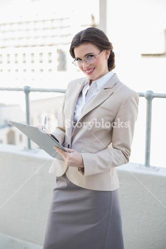 Pleased stylish brown haired businesswoman taking notes