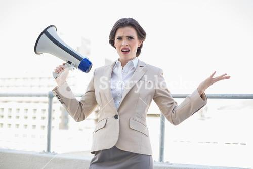 Irritated stylish brown haired businesswoman holding a megaphone