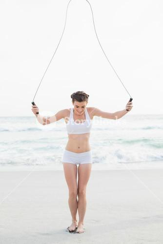 Dynamic slim brown haired model in white sportswear playing with a skipping rope