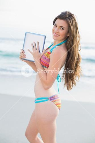Delighted slim brown haired model in coloured bikini holding a tablet pc