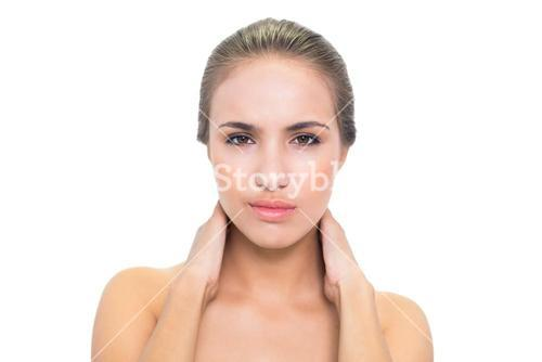 Frowning brunette woman having a sore neck