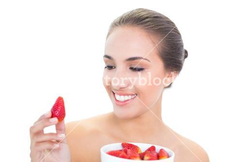 Young brunette woman smiling at a strawberry