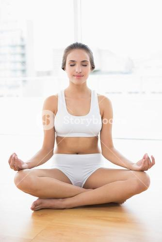 Peaceful brunette woman with closed eyes meditating