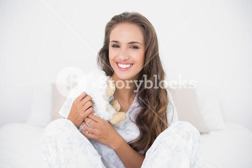 Smiling attractive brunette holding a soft toy