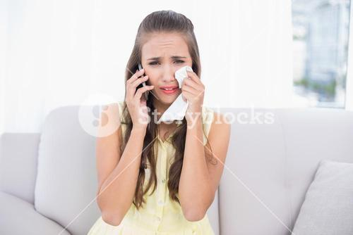 Sad young brunette holding tissue and mobile phone