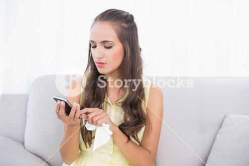 Upset young brunette holding mobile phone and tissue