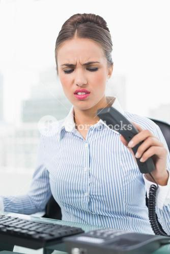 Angry brunette businesswoman hanging up the phone