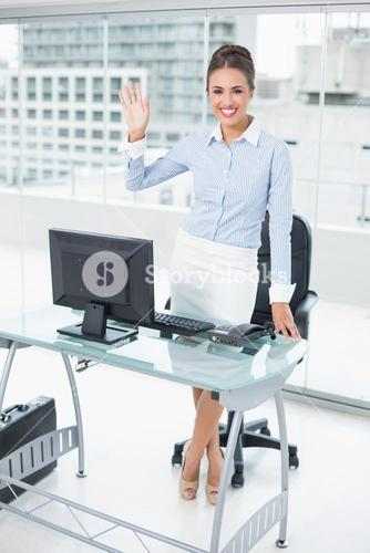 Smiling brunette businesswoman waving