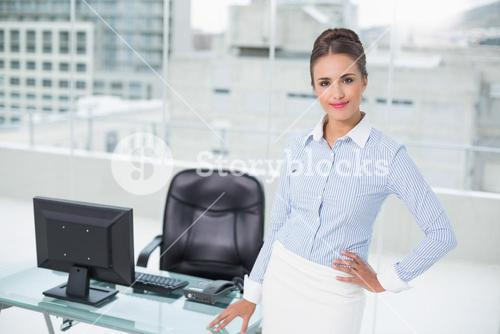Smiling businesswoman standing hand on hips