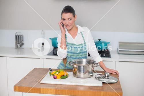 Smiling gorgeous woman wearing apron having a call