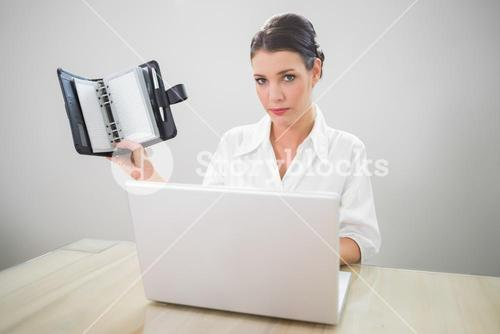 Serious businesswoman working on laptop holding datebook
