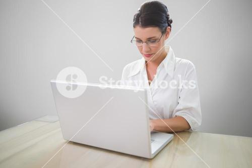Focused businesswoman with classy glasses posing