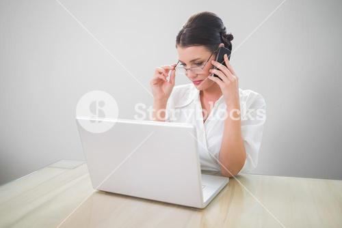 Seductive businesswoman with classy glasses phoning