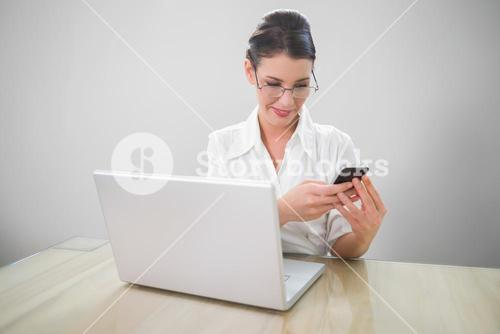Smiling businesswoman with classy glasses texting