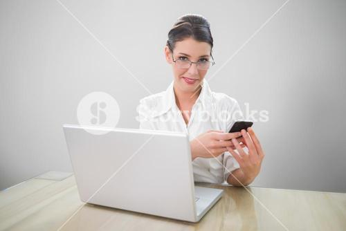 Cheerful businesswoman with classy glasses texting