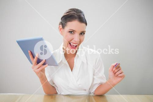 Enthusiastic pretty businesswoman shopping online