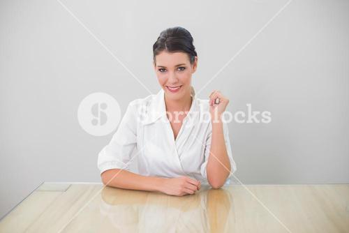 Smiling brown haired businesswoman posing
