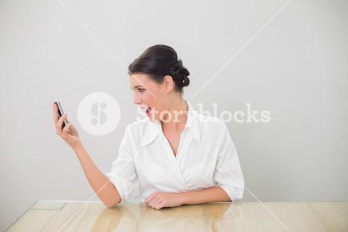 Surprised brown haired businesswoman text messaging