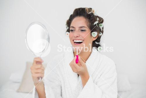 Laughing natural brunette putting lip gloss on