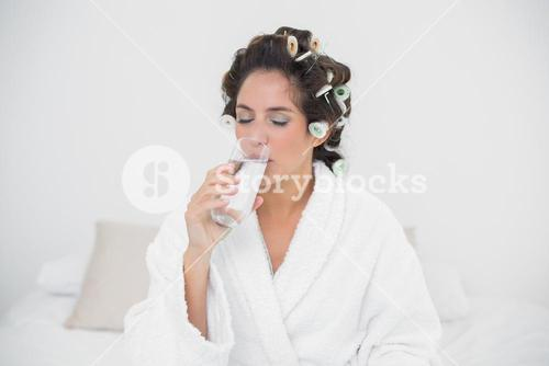 Peaceful natural brunette drinking glass of water