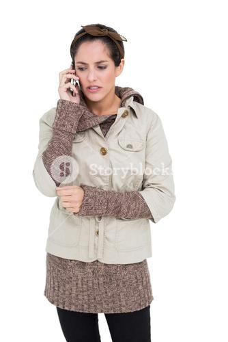 Upset cute brunette in winter fashion phoning