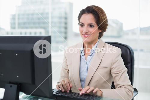 Smiling businesswoman sitting in front of computer