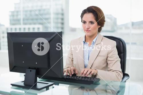 Stern businesswoman sitting in front of computer