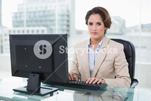 Stern businesswoman sitting looking at camera